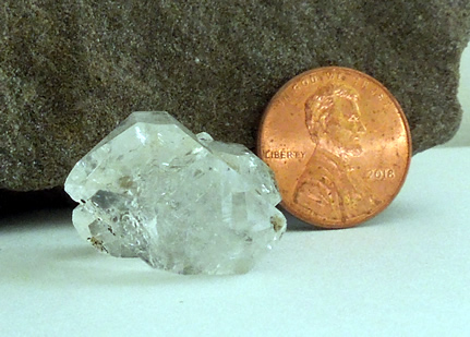 Quartz crystal with penny for size comparison.